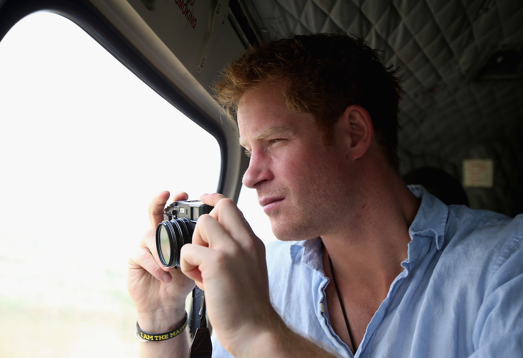 . Prince Harry takes a photograph out of the window of a Lesotho Army Helicopter on a Fuji X100s Camera as he travels over the Muluti Mountains on the way to a herd boy night school constructed by Sentebale on December 8, 2014 in Mokhotlong, Lesotho. (Photo by Chris Jackson - WPA Pool /Getty Images)
