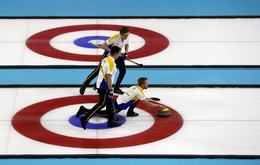 . Sweden\'s Skip Niklas Edin (C) throws a stone during the men\'s Bronze medal match between Sweden and China at the Ice Cube curling centre in Sochi on February 21, 2014 during the 2014 Sochi winter Olympics. ADRIAN DENNIS/AFP/Getty Images