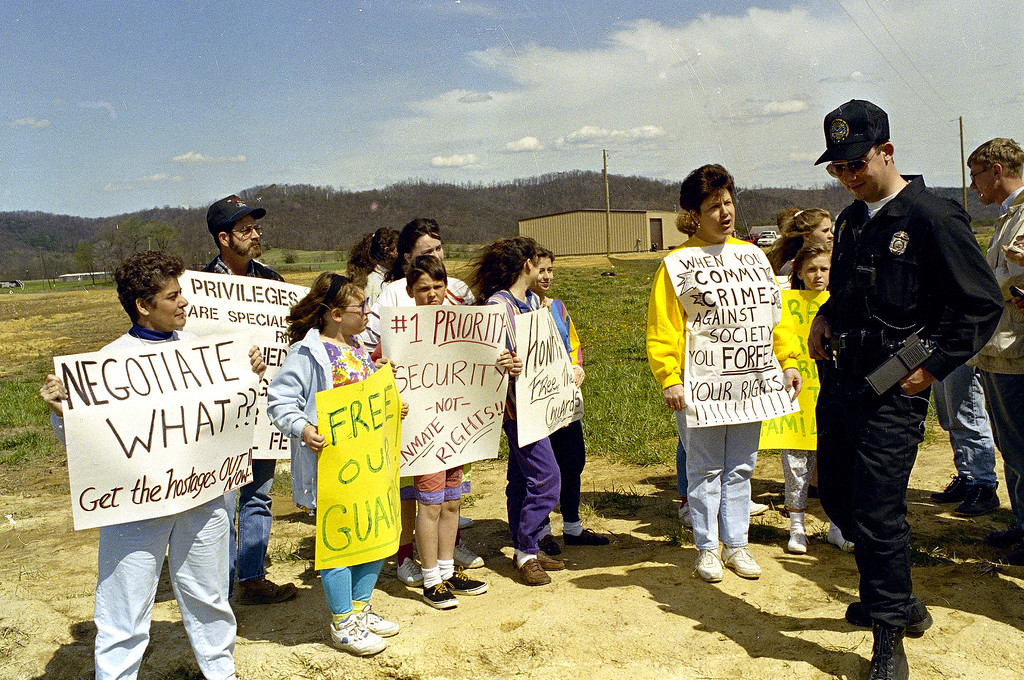 . An Ohio State Trooper stands with a group of people carrying signs supporting the hostages being held at the Southern Ohio Correctional Facility in Lucasville, Ohio, April 18, 1993.  The siege by inmates enters its second week.  (AP Photo/Lennox McLendon)
