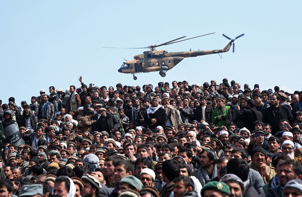 . An Afghan National Army (ANA) helicopter flies as Afghan men attend in the burial of Afghanistan\'s influential Vice President Mohammad Qasim Fahim during his funeral procession in Kabul, Afghanistan, Tuesday, March 11, 2014. Fahim, a leading commander in the alliance that fought the Taliban who was later accused with other warlords of targeting civilian areas during the country\'s civil war, died on Sunday, March 9, 2014. He was 57. (AP Photo/Massoud Hossaini)
