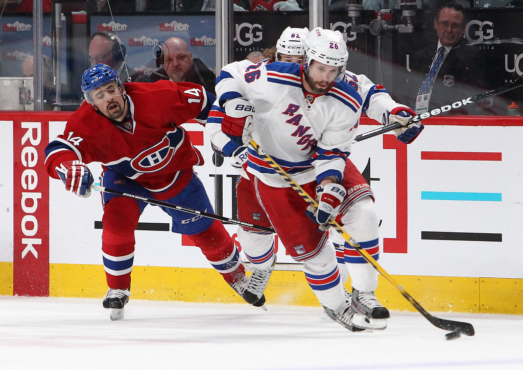 . Martin St. Louis #26 of the New York Rangers plays the puck against \\Tomas Plekanec #14 of the Montreal Canadiens during Game Five of the Eastern Conference Final in the 2014 NHL Stanley Cup Playoffs at Bell Centre on May 27, 2014 in Montreal, Canada.  (Photo by Francois Laplante/FreestylePhoto/Getty Images)