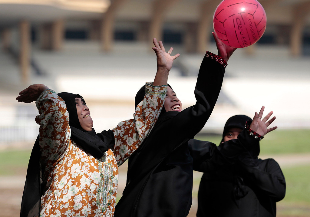 . Filipino women Muslims play as they celebrate Eid al-Fitr, marking the end of the holy month of Ramadan, at Manila\'s Rizal Park, Philippines Thursday, Aug. 8, 2013. (AP Photo/Aaron Favila)