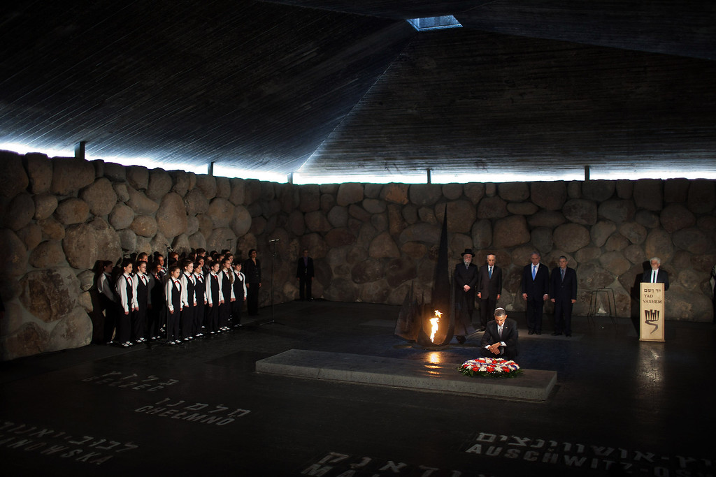 . U.S. President Barack Obama pays his respects in the Hall of Remembrance in front of Israel\'s President Shimon Peres, Israel\'s Prime Minster Benjamin Netanyahu, Chairman of the Yad Vashem Directorate Avner Shalev, Rabbi Yisrael Meir Lau and the Abnkor Children\'s Choir after marines layed a wreath on his behalf during his visit to the Yad Vashem on March 22, 2013 in Jerusalem, Israel. (Photo by Uriel Sinai/Getty Images)