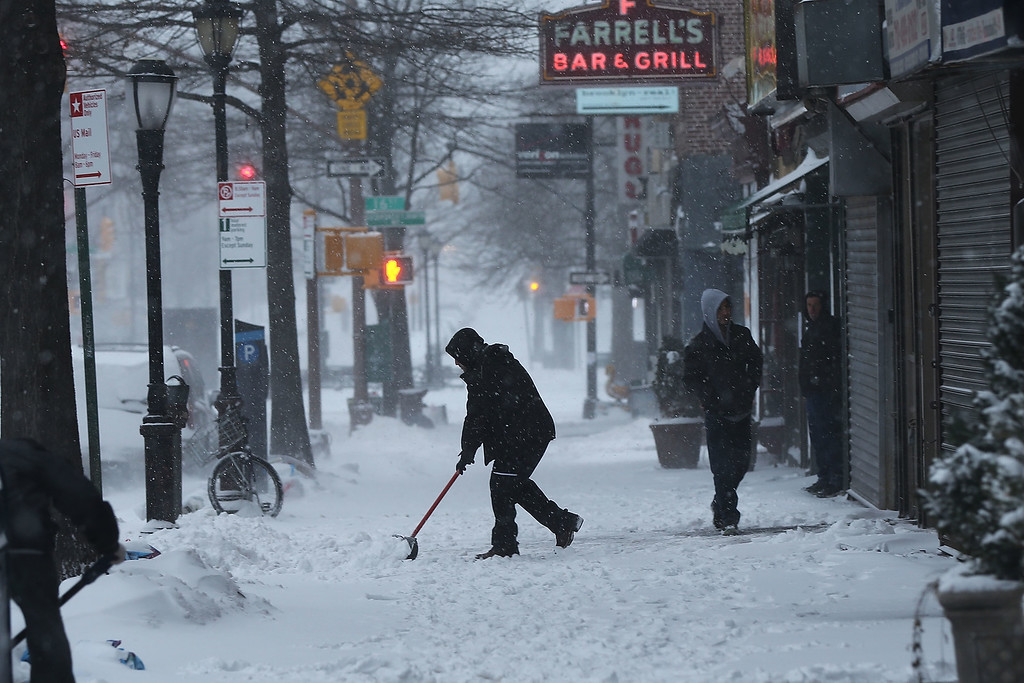 . A man clears snow in Brooklyn the morning after a major winter storm on January 27, 2015 in New York City. Despite dire predictions, New York City was spared the worst of the storm, receiving up to a foot of snow in some areas. Subway buses were closed overnight while roadways were open only to emergency vehicles.  (Photo by Spencer Platt/Getty Images)