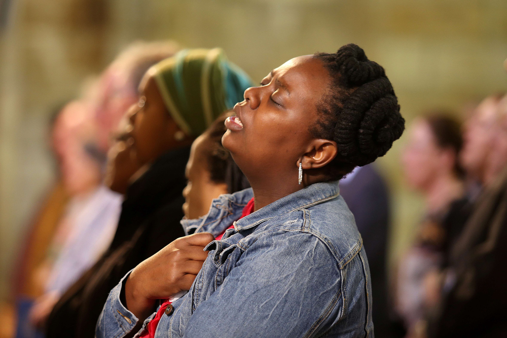 . A woman mourns during a mass celebrated a mass at St Georges Cathedral in Capetown on December 6, 2013 following the death of former South African President Nelson Mandela. Peace icon Nelson Mandela\'s wrinkled face beamed out from South African newspaper front pages today, as the Rainbow Nation\'s media strained to mark the momentousness of his death. JENNIFER BRUCE/AFP/Getty Images