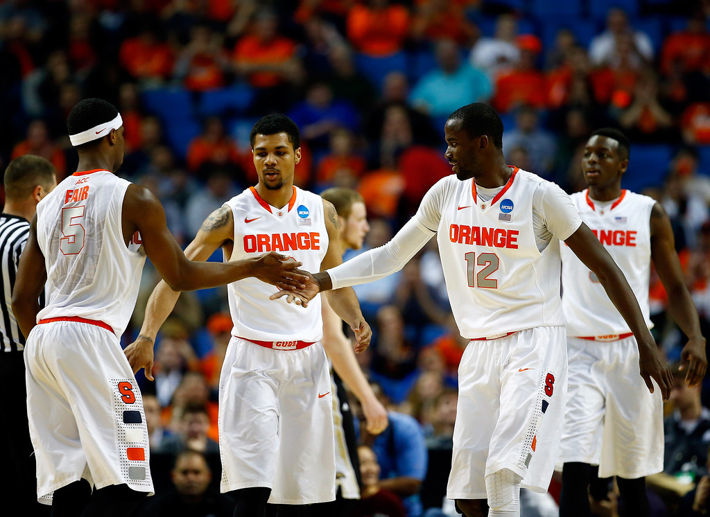 . BUFFALO, NY - MARCH 20: C.J. Fair #5 celebrates with Michael Gbinije #0 and Baye-Moussa Keita #12 of the Syracuse Orange against the Western Michigan Broncos during the second round of the 2014 NCAA Men\'s Basketball Tournament at the First Niagara Center on March 20, 2014 in Buffalo, New York.  (Photo by Jared Wickerham/Getty Images)