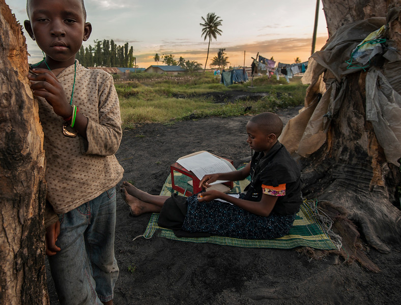 Two sisters doing their homework outside in the fresh evening air.  Tanzania, 2019.