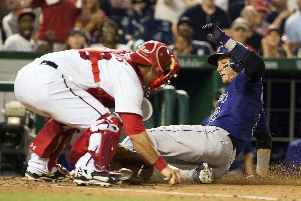 . Colorado Rockies Troy Tulowitzki slides safely past Washington Nationals catcher Wilson Ramos, left, on a sacrifice fly hit by teammate Ryan Wheeler during the sixth inning of a baseball game at Nationals Park, on Monday, June 30, 2014, in Washington. (AP Photo/ Evan Vucci)
