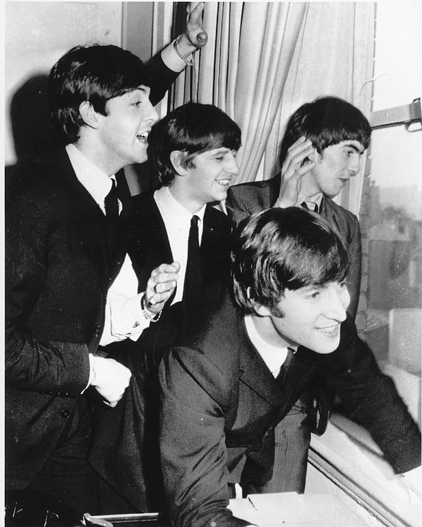 . The Beatles wave to fans assembled below their Plaza Hotel window after they arrived in New York City on Feb. 7, 1964 for a short tour of the United States. From left to right are, Paul McCartney, Ringo Starr, John Lennon, and George Harrison. (AP Photo)