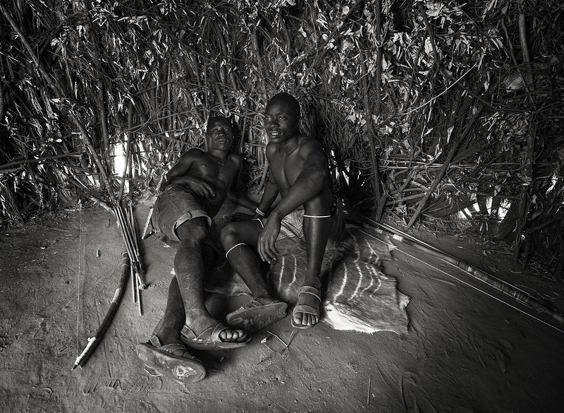 Two young men from the Hadzabe tribe inside their temporary hut.  Tanzania, 2019.