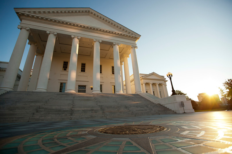 White columns of the Virginia State Capitol as the sun rises over Richmond.