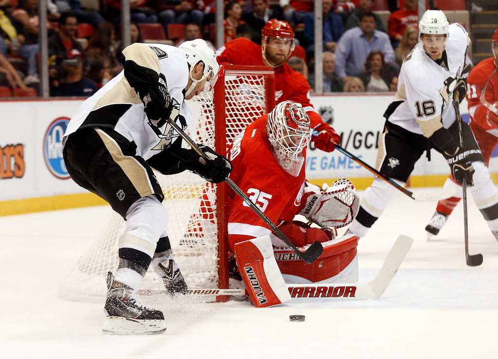 . Detroit Red Wings goalie Jimmy Howard (35) stops a Pittsburgh Penguins\' Pascal Dupuis (9) shot in the first period of a NHL preseason hockey game in Detroit Wednesday, Oct. 1, 2014. (AP Photo/Paul Sancya)