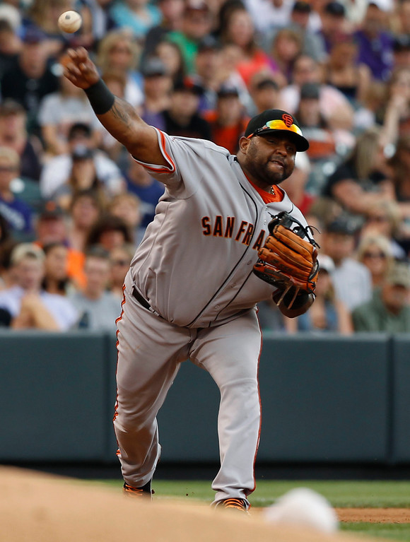 . San Francisco Giants third baseman Pablo Sandoval throws to first base to put out Colorado Rockies\' Nolan Arenado in the fourth inning of a baseball game in Denver on Saturday, June 29, 2013. (AP Photo/David Zalubowski)