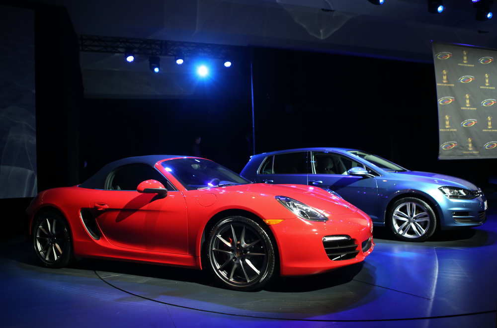 Description of . A Porsche Boxster/Cayman (L), is displayed before being named the 2013 World Performance Car of the Year at the New York Auto Show on March 28, 2013 in New York City. It was the second consecutive year that Porsche has won the prestigious title and the third overall.  (Photo by John Moore/Getty Images)