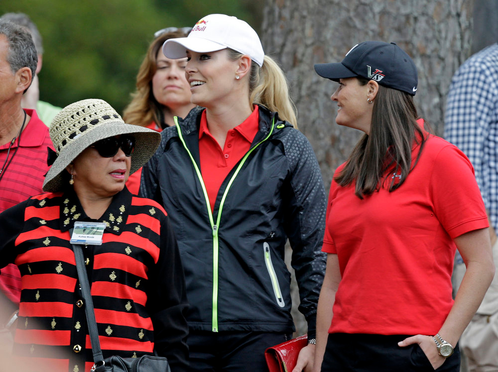 Description of . Tiger Woods' mother Kultida Woods, left, skier Lindsey Vonn and her physical therapist Lindsay Winninger, right, watch Woods during the fourth round of the Masters golf tournament Sunday, April 14, 2013, in Augusta, Ga. (AP Photo/David J. Phillip)