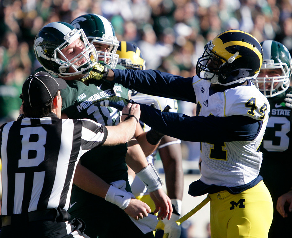. Michigan\'s Delano Hill, right, shoves Michigan State quarterback Connor Cook during the first quarter of an NCAA college football game, Saturday, Oct. 25, 2014, in East Lansing, Mich. Hill was penalized on the play. (AP Photo/Al Goldis)