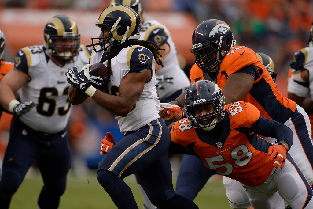 . DENVER, CO. - August 24: The outside linebacker Von Miller (58) of the Denver Broncos gets to running back Daryl Richardson (26) of the St. Louis Rams behind the line of scrimmage for a loss during the 3rd pre-season game of the season at Sports Authority Field at Mile High. August 24, 2013 Denver, Colorado. (Photo By Joe Amon/The Denver Post)