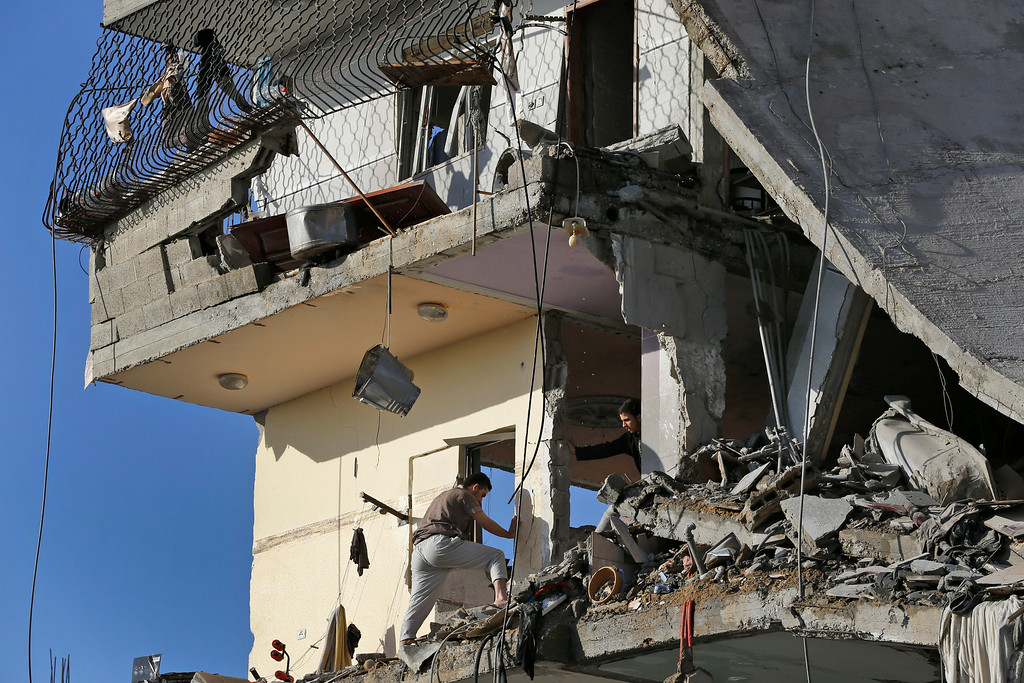 . Palestinians inspect damages of the el-Yazje family apartment building which was destroyed following an overnight Israeli missile strike in Gaza City, Thursday, July 17, 2014. The Israeli military says it has struck 37 targets in Gaza ahead of a five-hour humanitarian cease-fire meant to allow civilians to stock up after 10 days of fighting. The Gaza Interior Ministry says four people were killed and that a 75-year-old woman died of wounds from the day before. The Israeli army says Hamas fired 11 rockets at Israel early Thursday. Palestinian health officials say that in total, at least 225 Palestinians have been killed. On the Israeli side, one man was killed since July 8. (AP Photo/Lefteris Pitarakis)