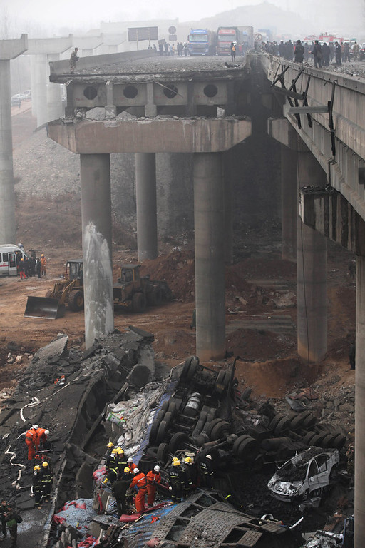 . Rescuers (bottom) work at the scene of the collapsed Yichang bridge near the city of Sanmenxia, central China\'s Henan province, on February 1, 2013 after a fireworks-laden truck exploded as it crossed the bridge killing 26 people as the structure collapsed and vehicles plummeted to the ground, state-run media reported. An 80-meter long part of the bridge collapsed and six vehicles had been retrieved from the debris, China\'s official news agency Xinhua said. The bridge near the city of Sanmenxia is on the G30 expressway, the longest road in China, which stretches for nearly 4,400 kilometers (2,700 miles) from China\'s western border with Kazakhstan to the eastern Yellow Sea. AFP PHOTO STR/AFP/Getty Images