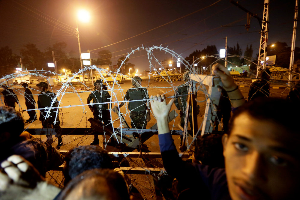 . Egyptian protesters stand behind barbed wire on a road leading to the presidential palace during a protest against Egyptian President Mohammed Morsi, in Cairo, Egypt, Thursday, Dec. 6, 2012. The Egyptian army has deployed tanks outside the presidential palace in Cairo following clashes between supporters and opponents of Mohammed Morsi that left several people dead and hundreds wounded. (AP Photo/Hassan Ammar)