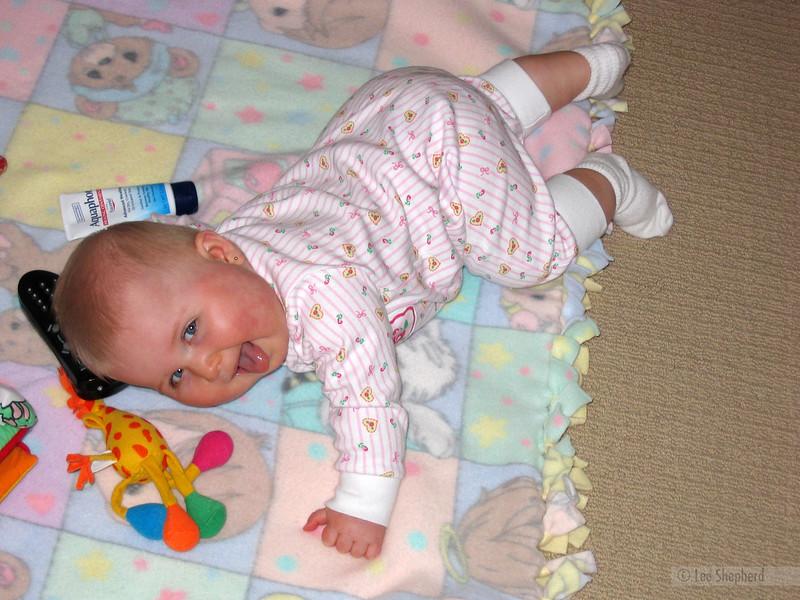 Blonde beat-box baby breakdances by brown bear blanket.