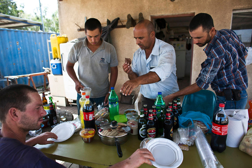 . Nadav (C), the chief cowboy of the Yonatan herd, and his team eat at the end of the day after selling their cattle, just outside Moshav Yonatan, a collective farming community, about 2 km (1 mile) south of the ceasefire line between Israel and Syria in the Golan Heights May 21, 2013.  REUTERS/Nir Elias