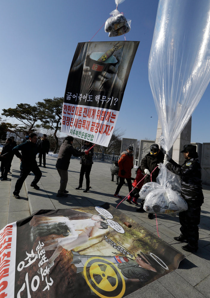 ". North Korean defectors and South Korean activists prepare to launch helium balloons carrying leaflets, seen at bottom of balloon, during an anti-North Korea rally denouncing North Korea\'s third nuclear test at the Imjingak Pavilion near the border village of  Panmunjom, in Paju, north of Seoul, South Korea, Saturday, Feb. 16, 2013. They flew the 200,000 propaganda leaflets across the border to denounce the nuclear test and late leader Kim Jong Il\'s birthday on Saturday. The letters read ""Nuclear weapons when starving to death?\"" (AP Photo/Lee Jin-man)"