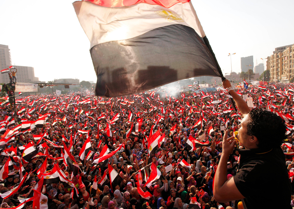 """. Protesters against Egyptian President Mohamed Mursi wave national flags in Tahrir Square in Cairo July 3, 2013. The Egyptian president\'s national security adviser said on Wednesday that a \""""military coup\"""" was under way and army and police violence was expected to remove pro-Mursi demonstrators. REUTERS/Mohamed Abd El Ghany"""