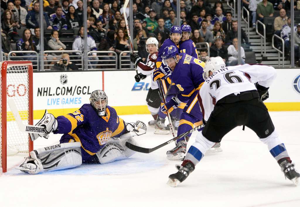 . LOS ANGELES, CA - FEBRUARY 23:  Jonathan Quick #32 of the Los Angeles Kings makes a save off a shot from Paul Stastny #26 of the Colorado Avalanche as Jake Muzzin #6 of the Los Angeles Kings looks for a rebound during the game against the Colorado Avalanche at Staples Center on February 23, 2013 in Los Angeles, California.  (Photo by Harry How/Getty Images)