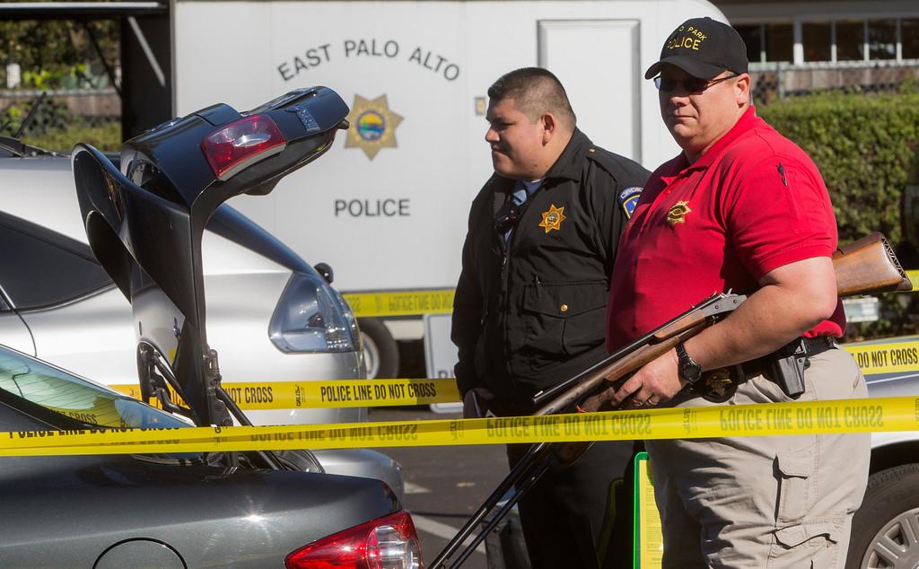 . A Menlo Park police officer removes gun from a car as the Peninsula cities of Palo Alto, Menlo Park and East Palo Alto police held a gun buyback. (John Green/Staff)