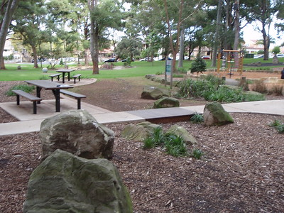 timber bridge in concrete path and picnic tables with benches