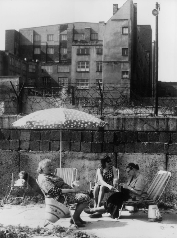 . A West Berlin family using the Berlin Wall as a windbreak and suntrap on a sunny day in spring.   (Photo by Keystone/Getty Images)