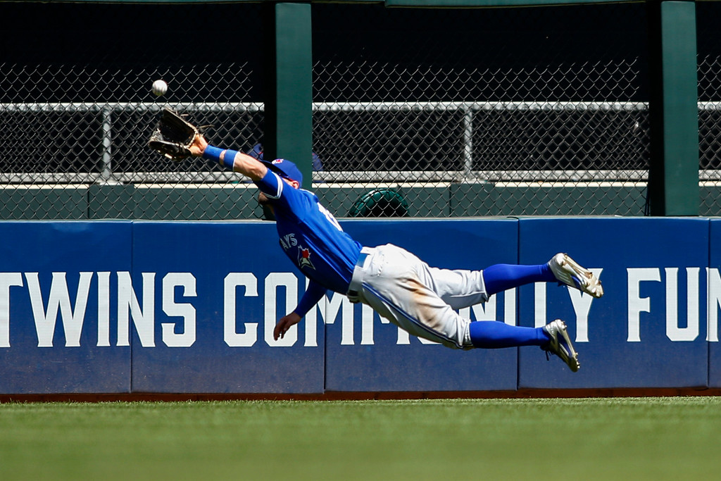 . Toronto Blue Jays center fielder Kevin Pillar dives for and catches a fly ball hit by Minnesota Twins\' Brian Dozier in the fifth inning of a baseball game Sunday, May 22, 2016, in Minneapolis. (AP Photo/Bruce Kluckhohn)