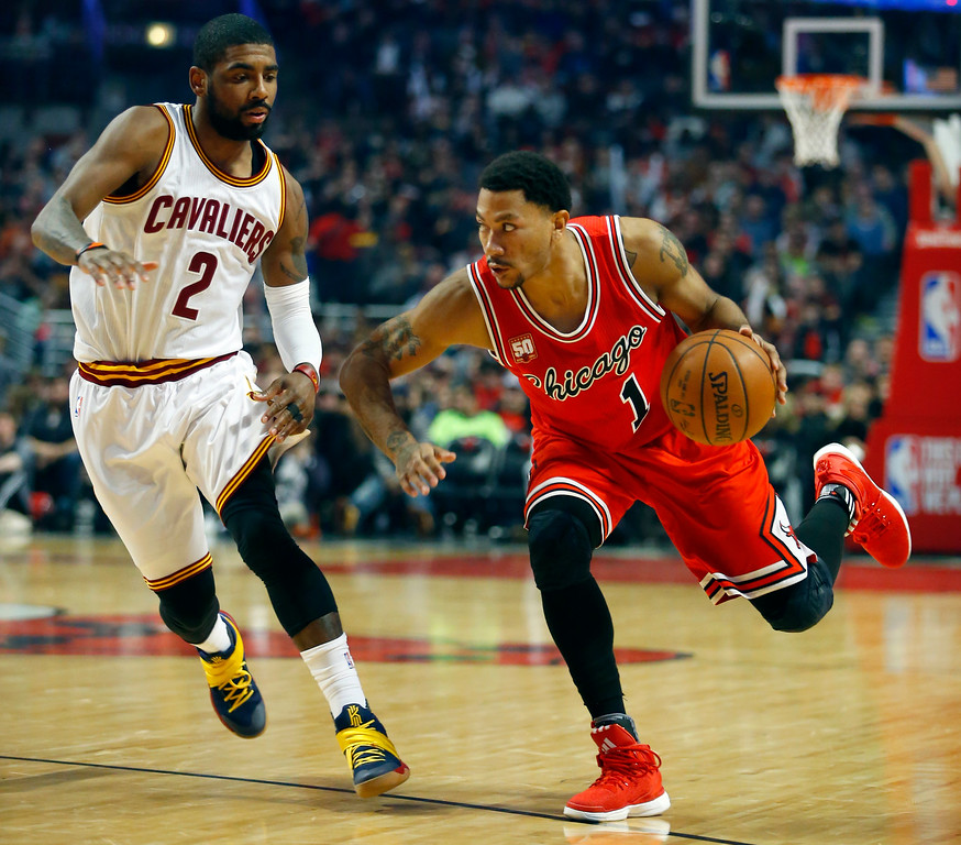 . Chicago Bulls guard Derrick Rose (1) dribbles past Cleveland Cavaliers guard Kyrie Irving (2) during the second half of an NBA basketball game in Chicago on Saturday, April 9, 2016. (AP Photo/Jeff Haynes)