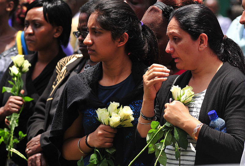 . Relatives of victims of the Westgate Mall attack, carry flowers  during a ceremony marking the first anniversary of the attack, outside the Westgate mall in Nairobi on September 21, 2014. At least 67 people were killed and scores wounded when a small group of Al-Qaeda affiliated fighters stormed the Westgate mall on September 21 2013. CARL DE SOUZA/AFP/Getty Images