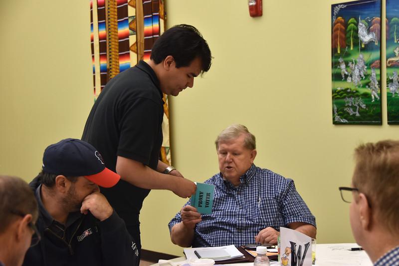 Angel distributes a proxy ballot to Fr. Bill