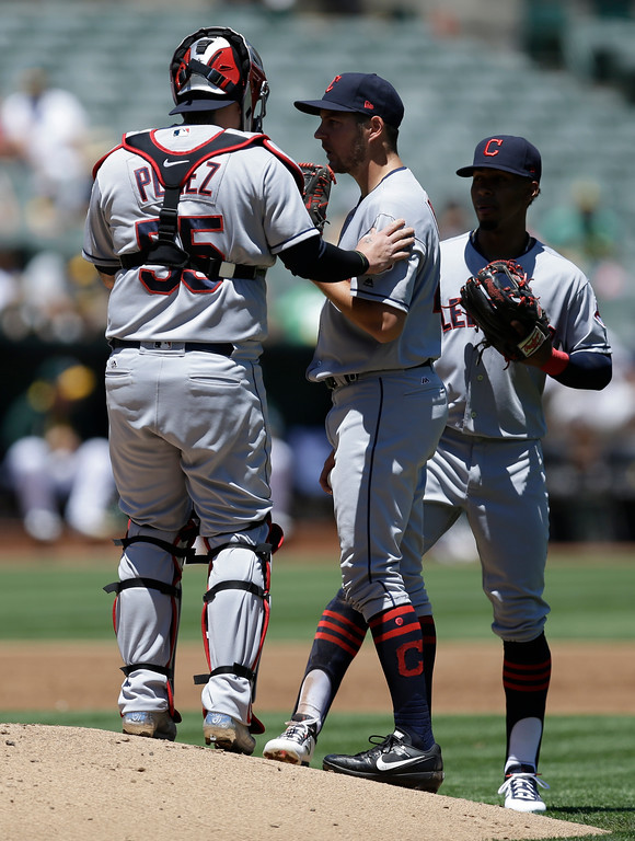 . Cleveland Indians catcher Roberto Perez, left, speaks to pitcher Trevor Bauer, center, in the first inning of a baseball game against the Oakland Athletics, Sunday, July 16, 2017, in Oakland, Calif. (AP Photo/Ben Margot)