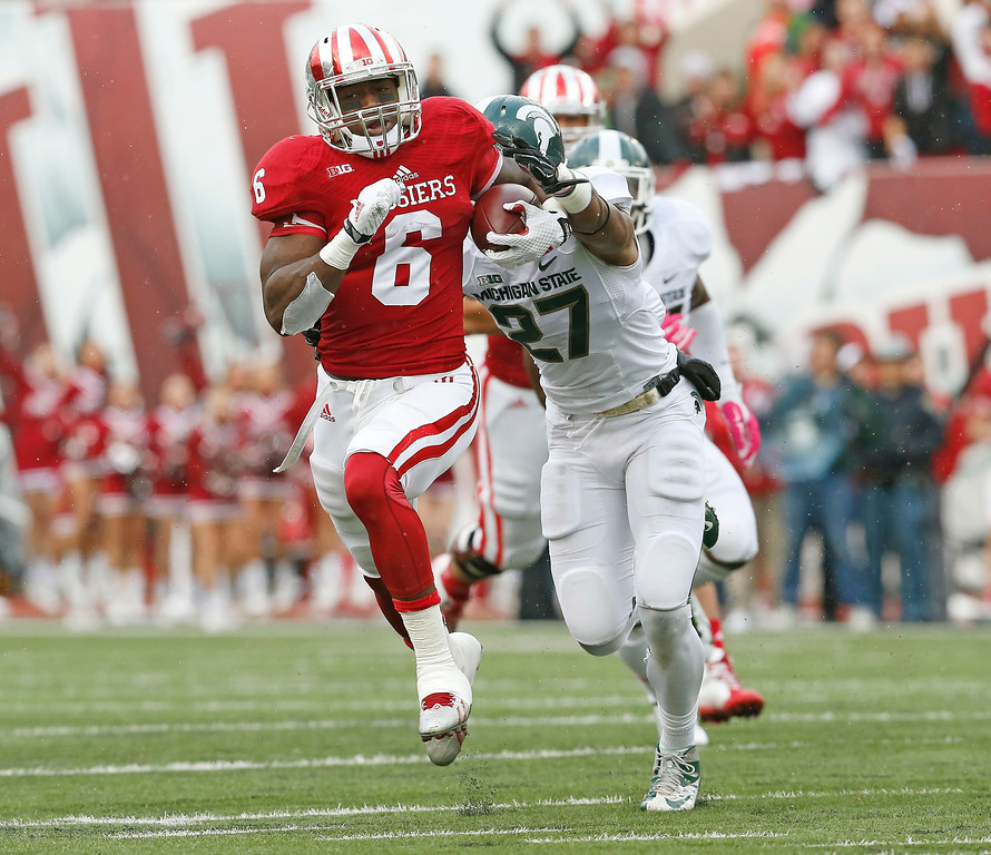 . Indiana running back Tevin Coleman (6) tries to escape Michigan State safety Kurtis Drummond (27) in the first half of an NCAA college football game in Bloomington, Ind., Saturday, Oct. 18, 2014. (AP Photo/Sam Riche)