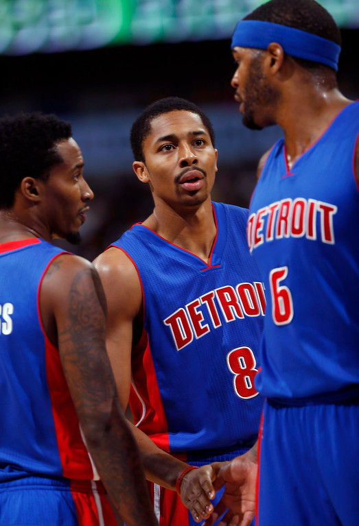 . Detroit Pistons rookie guard Spencer Dinwiddie, center, who was drafted this year from the University of Colorado, confers with teammates Brandon Jennings, left, and Josh Smith while facing the Denver Nuggets in the first quarter of an NBA basketball game in Denver on Wednesday, Oct. 29, 2014. (AP Photo/David Zalubowski)