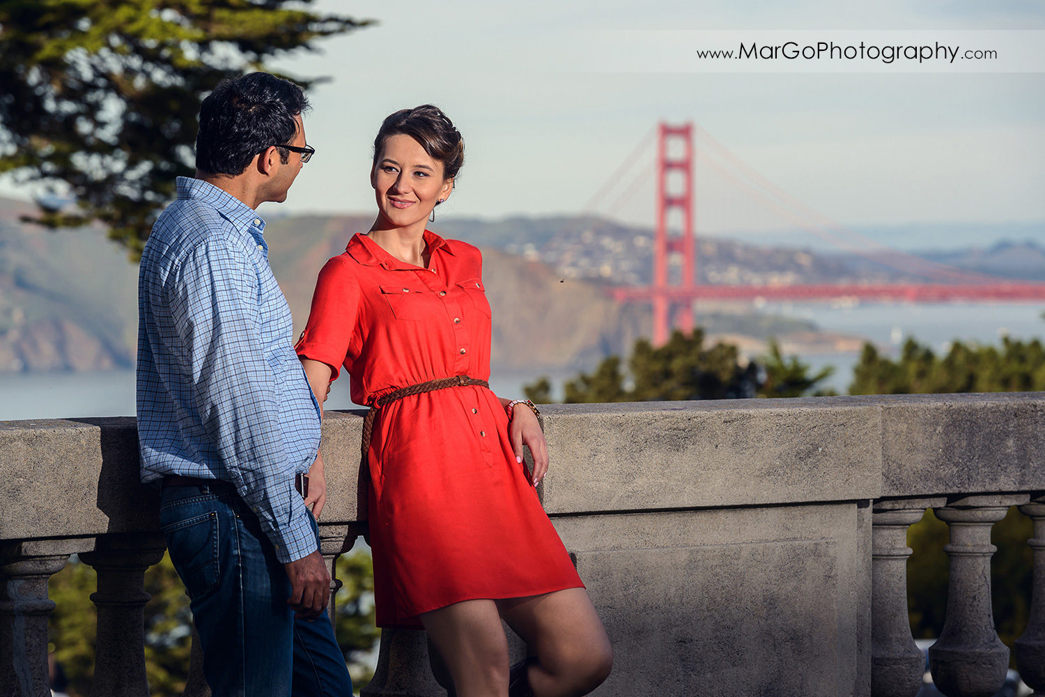 man in blue shirt and woman in red dress standing on the balcony with Golden Gate Bridge in the background during engagement session at San Francisco Legion of Honor