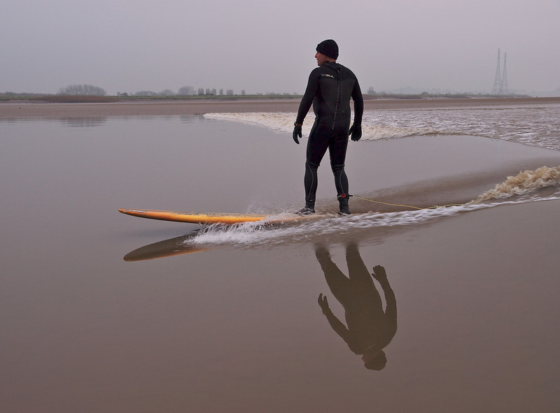 Beautiful reflections as Steve rides the Severn Bore wave.