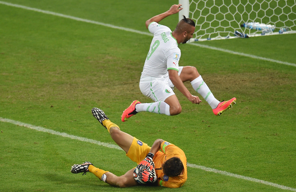 . Algeria\'s forward Nabil Ghilas (top) jumps over South Korea\'s goalkeeper Jung Sung-Ryong as he catches the ball during the Group H football match between South Korea and Algeria at the Beira-Rio Stadium in Porto Alegre during the 2014 FIFA World Cup on June 22, 2014.    PEDRO UGARTE/AFP/Getty Images