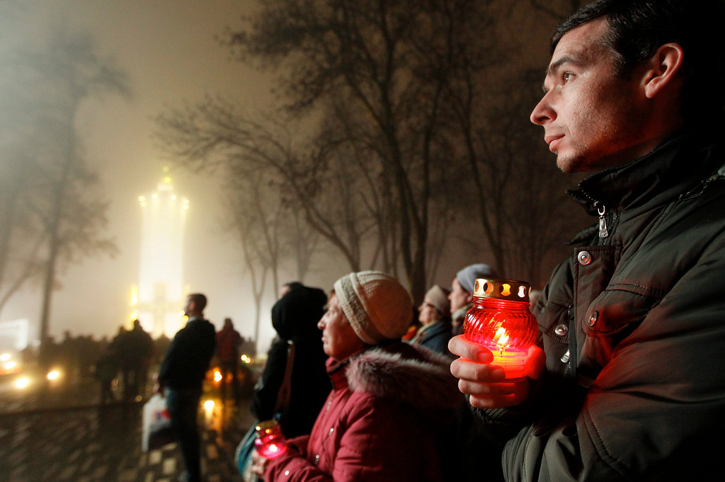 . Ukrainians hold candles during a memorial ceremony near of a monument to the victims of the Great Famine in Kiev, 23 November 2013.  EPA/SERGEY DOLZHENKO
