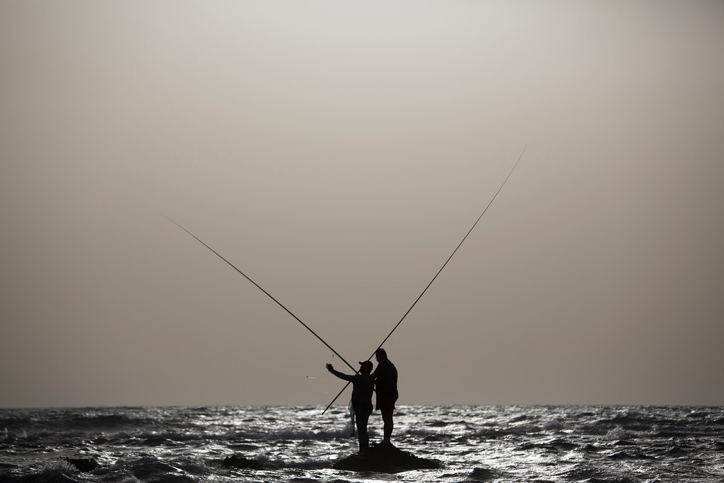 . Two fishermen cast their fishing pole fas they stand on a rock in the Mediterranean Sea near Michmoret, Israel, Monday, May 16, 2016. (AP Photo/Ariel Schalit)