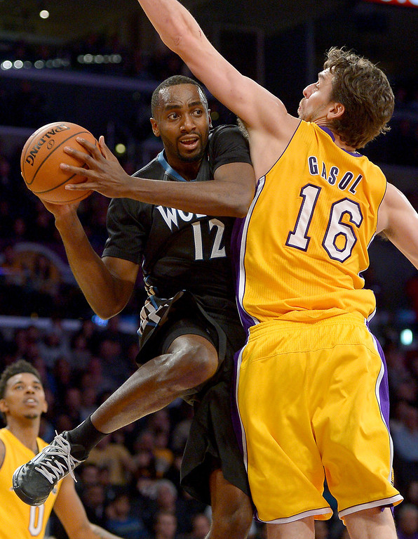. The Timberwolves\' Luc Richard Mbah a Moute looks to pass around the Lakers\' Pau Gasol along the baseline, Friday, December 20, 2013, at Staples Center. (Photo by Michael Owen Baker/L.A. Daily News)