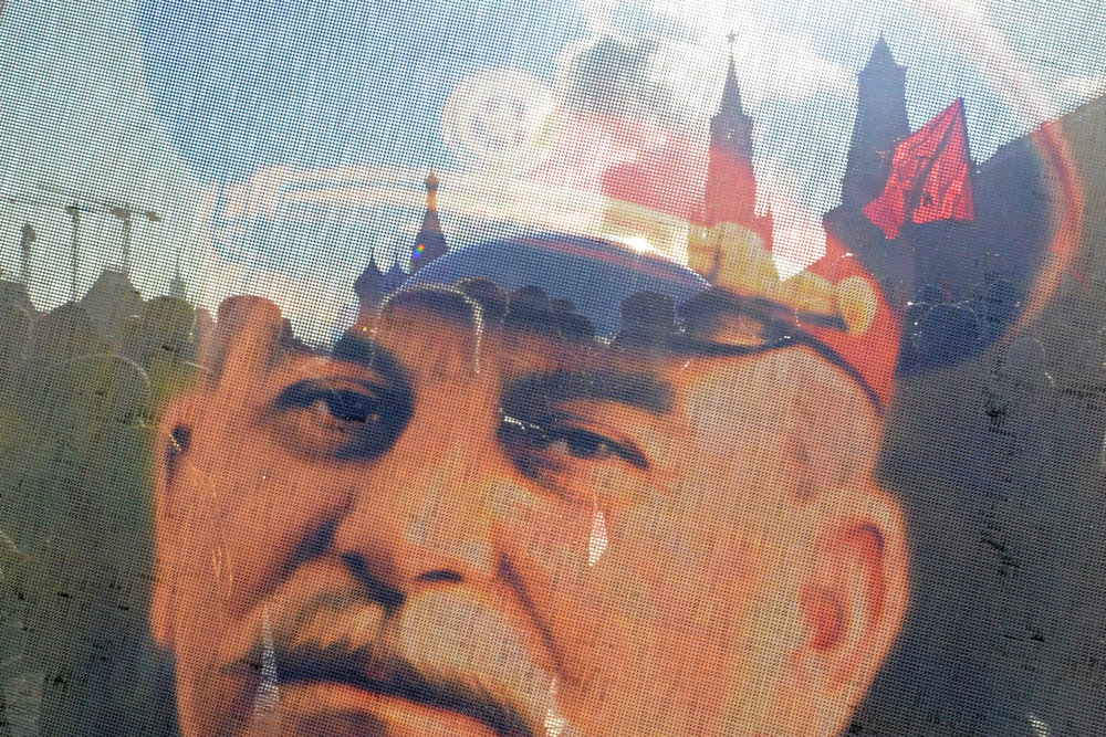 . Russian Communists and their supporters are seen through a transparent portrait of Soviet dictator Josef Stalin as they lay flowers at his tomb at the Red Square in Moscow on March 5, 2013 to mark the 60th anniversary of Stalin\'s death. Russia marks today 60 years since the death of Stalin with attitudes split about whether to view him as a tyrant who slaughtered millions or a national savior who helped turn the country into a global superpower that emerged victorious in World War II.  KIRILL KUDRYAVTSEV/AFP/Getty Images