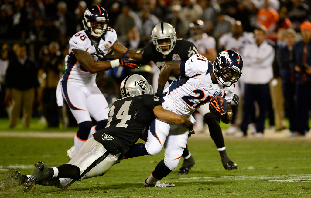 . Denver Broncos running back Ronnie Hillman #21 is dragged down by Oakland Raiders strong safety Mike Mitchell #34  in the first quarter at the O.co Coliseum, in Oakland , CA December 06, 2012.      Joe Amon, The Denver Post