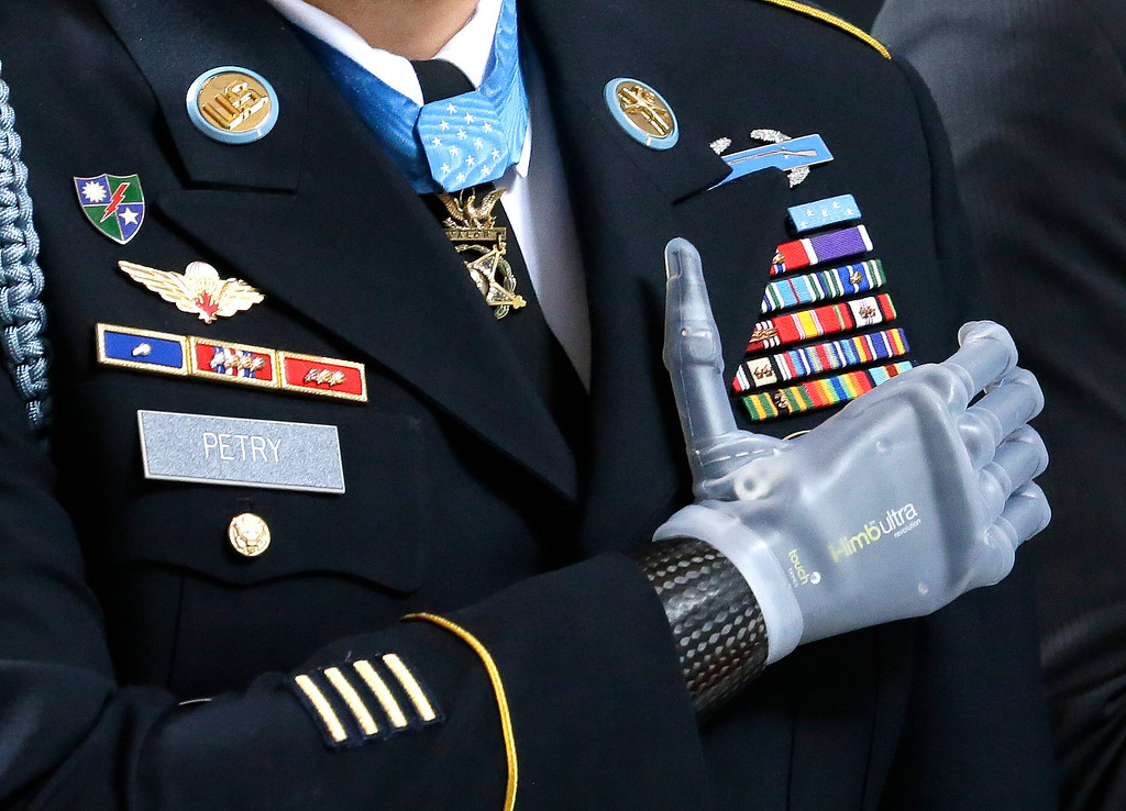 """. Medal of Honor recipient Sgt. 1st Class Leroy Petry stands with his prosthetic hand over his heart, wearing his Medal of Honor during the \""""Pledge of Allegiance\"""" at the Capitol in Olympia, Wash. on Wednesday, April 2, 2014, during a ceremony to honor him and other recipients of the Medal of Honor from Washington state. Petry lost his hand in 2008 when an enemy grenade he was throwing away from fellow soldiers detonated while in combat in Afghanistan. (AP Photo/Ted S. Warren, File)"""