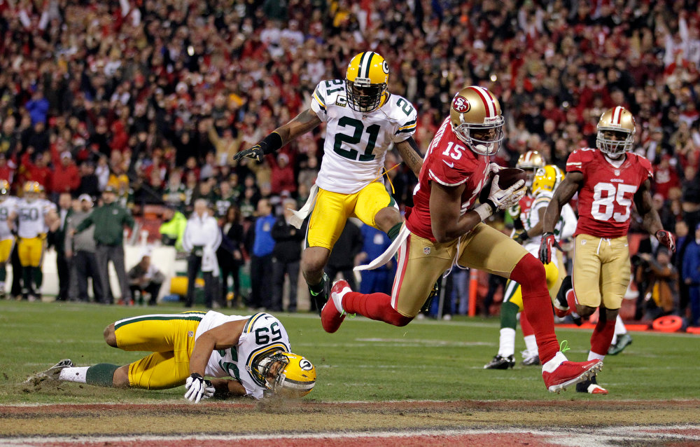 Description of . San Francisco 49ers wide receiver Michael Crabtree (15) scores a touchdown as Green Bay Packers inside linebacker Brad Jones (59), and strong safety Charles Woodson (21) move in to stop him in the first half of an NFC divisional playoff NFL football game in San Francisco, Saturday, Jan. 12, 2013. (AP Photo/Tony Avelar)