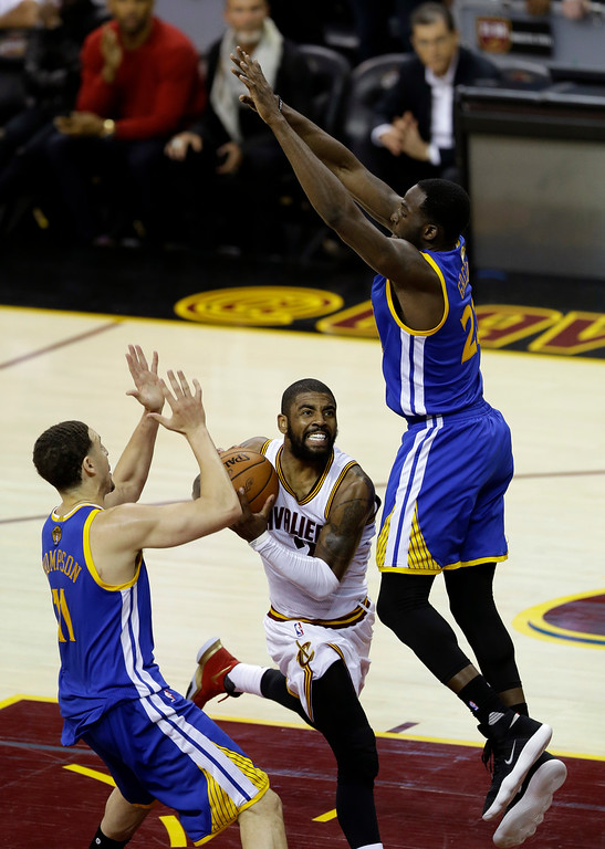 . Cleveland Cavaliers guard Kyrie Irving, center, drives between Golden State Warriors guard Klay Thompson, left, and Draymond Green, right, in the second half of Game 4 of basketball\'s NBA Finals in Cleveland, Friday, June 9, 2017. (AP Photo/Tony Dejak)